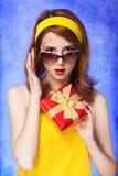 Amerikansk redheadflicka i solglasögon med gåvan. Royaltyfri Bild