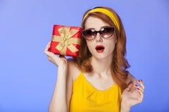 Amerikansk redheadflicka i solglasögon med gåvan. Arkivbilder