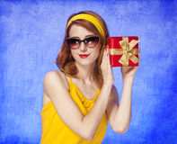 Amerikansk redheadflicka i solglasögon med gåvan. Royaltyfri Foto