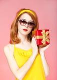 Amerikansk redheadflicka i solglasögon med gåvan. Royaltyfria Foton