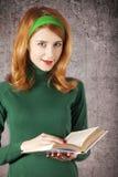 Amerikansk redheadflicka med boken. Royaltyfri Fotografi