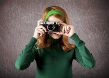 Amerikansk redheadflicka med kameran. Arkivbild