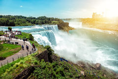 Amerikansk sida av Niagara Falls, NY, USA Turister som tycker om härlig sikt till Niagara Falls under varm solig sommardag Arkivfoton