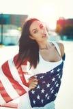 Amerikansk sinnlig skönhet som täcktes av stjärnan, spangled banret i sunse Arkivfoto