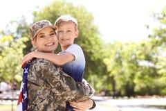 Amerikansk soldat med hennes son utomhus Militärtjänst royaltyfri foto