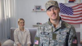 Amerikansk soldat som ler på kameran, stolt fru som sitter på soffan mot USA-flagga lager videofilmer