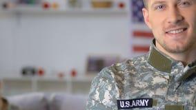 Amerikansk soldat som ser kameran, militär fru och sittande bakgrund för dotter lager videofilmer