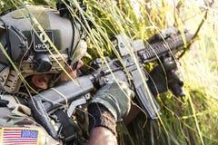 Amerikansk soldat som siktar hans gevär på gräset arkivbild