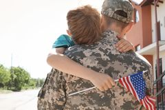 Amerikansk soldat som utomhus kramar med hans son royaltyfria foton