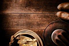 Amerikansk västra rodeocowboy Hat och kugghjulbakgrund Arkivfoton
