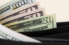 Amerikanska dollar är delvist synliga med en handväska arkivfoto