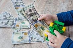 Amerikanska dollar, en leksakbil och händer på en grå bakgrund royaltyfri fotografi