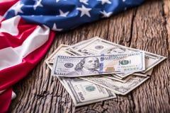 Amerikanska dollar en USA-flagga Stäng sig upp av amerikanska flaggan och kontanta pengar för dollar på gammalt ekträ Arkivbild