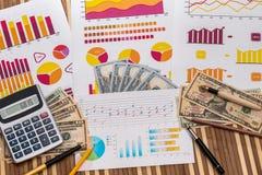 Amerikanska dollar på affärsgrafer med pennan och räknemaskinen arkivbild