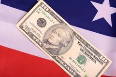 Amerikanska dollar på amerikanska flaggan Fotografering för Bildbyråer