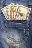 Amerikanska dollarräkningar i fick- bakgrund för jeans Arkivbild