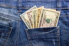 Amerikanska dollarräkningar i fick- bakgrund för jeans Arkivfoton