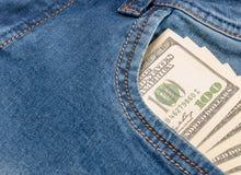 Amerikanska dollarräkningar i fick- bakgrund för jeans Royaltyfria Bilder