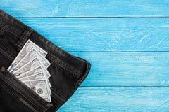 Amerikanska dollarräkningar i jeans stoppa i fickan på blå träbakgrund med kopieringsutrymme för din text Top beskådar Royaltyfri Fotografi