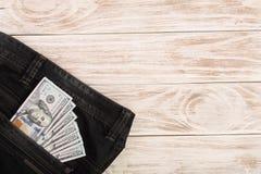 Amerikanska dollarräkningar i jeans stoppa i fickan på vit träbakgrund med kopieringsutrymme för din text Top beskådar Royaltyfri Fotografi