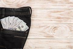 Amerikanska dollarräkningar i jeans stoppa i fickan på vit träbakgrund med kopieringsutrymme för din text Top beskådar Arkivbilder