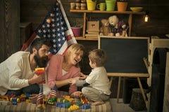amerikanska drömmen Lycklig familjlek med färgrika konstruktör- och leksakflaggor Föräldrar som lutar in mot son på soffan vänd Royaltyfri Fotografi