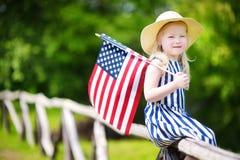 Amerikanska flaggan för hatt för förtjusande liten flicka bärande hållande utomhus på härlig sommardag Royaltyfri Fotografi