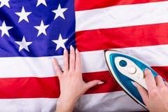 Amerikanska flaggan för trycka på för kvinnahänder med ett järn Visuellt begrepp av förberedelsen för självständighetsdagen fjärd Arkivbilder