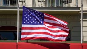 Amerikanska flaggan fladdrar på pol framme av byggnad, patriotism, demokrati arkivfoto