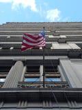 Amerikanska flaggan, i att vinka på en blåsig dag, sikt som ser rak upp från direkt under, framme av historisk kontorsbyggnadfasa arkivbilder