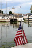 Amerikanska flaggan i hamn med fartyg och fyren Royaltyfri Bild