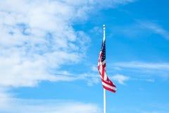 Amerikanska flaggan med himlen är full av moln i den regniga säsongen Arkivbild