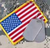 Amerikanska flaggan med hundetiketter på kamouflage Arkivfoton