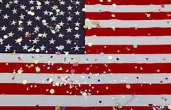 Amerikanska flaggan med många färgrika konfettier under det amerikanskt ho Fotografering för Bildbyråer