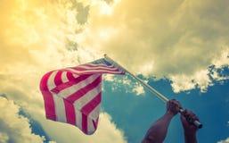 Amerikanska flaggan med stjärnor och band rymmer med händer mot blått Arkivfoton