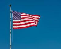 Amerikanska flaggan mot en klar blå Sky Royaltyfri Bild