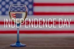 Amerikanska flaggan och exponeringsglas av vitt vin, 4th av Juli bakgrund Royaltyfri Foto