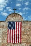 Amerikanska flaggan och träkors på en tegelstenbyggnad Arkivfoton