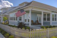 Amerikanska flaggan och vitposteringstaket på hem fotografering för bildbyråer