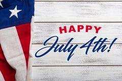 Amerikanska flaggan på en vit sliten träbakgrund med den Juli 4th hälsningen Arkivbild