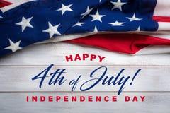 Amerikanska flaggan på en vit sliten träbakgrund med den Juli 4th hälsningen Royaltyfria Bilder