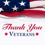 Amerikanska flaggan på en vit sliten träbakgrund med hälsning för veterandag royaltyfri foto