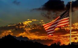 Amerikanska flaggan på flaggstången som framme vinkar i vindamerikanska flaggan av ljus himmel Arkivfoto