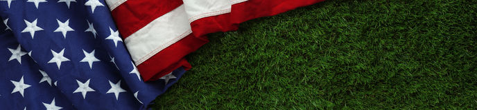 Amerikanska flaggan på gräs bakgrund för dag för för Memorial Day eller veteran` s arkivfoto