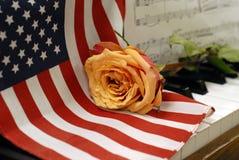 Amerikanska flaggan på pianotangenter med den guld- rosen och musik gör poäng Arkivbilder
