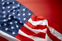 Amerikanska flaggan på röd bakgrund Arkivfoto