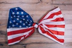 Amerikanska flaggan som binds i en fnuren, på den mörka träväggen Visuellt begrepp av förberedelsen för självständighetsdagen fjä Arkivbild