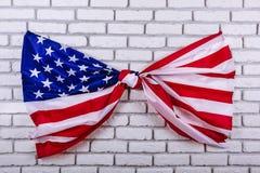 Amerikanska flaggan som binds i en fnuren, på en vit tegelstenvägg Visuellt begrepp av förberedelsen för självständighetsdagen fj Arkivbilder