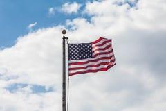Amerikanska flaggan som blåser i vind under moln Arkivfoton