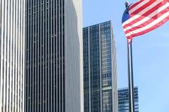 Amerikanska flaggan som vinkar förbi New York skyskrapor Arkivbild